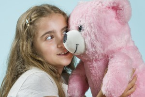 Happy girl smiles with her pink tedy bear. She loves teddy bear and her eyes looks it. She is 8 years old. Positive human face expression. Isolated on light blue background. Studio shot.